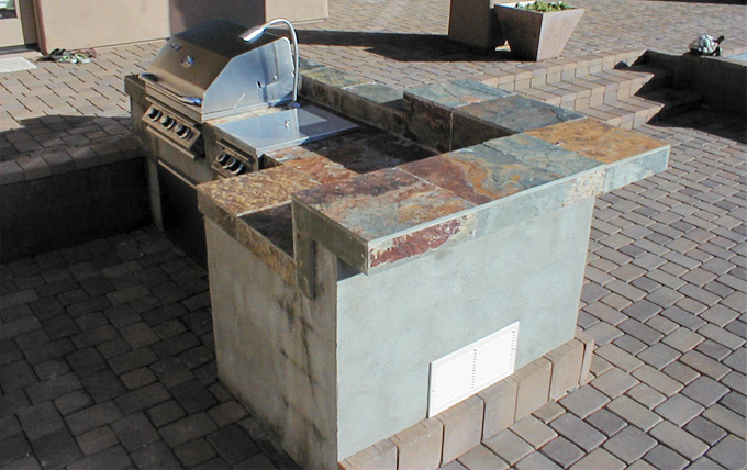 Stainless Steel Barbecue With Raised Bar Top And Slate Tile